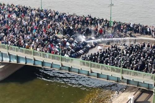 Protestors kneel in prayer in response to water cannons