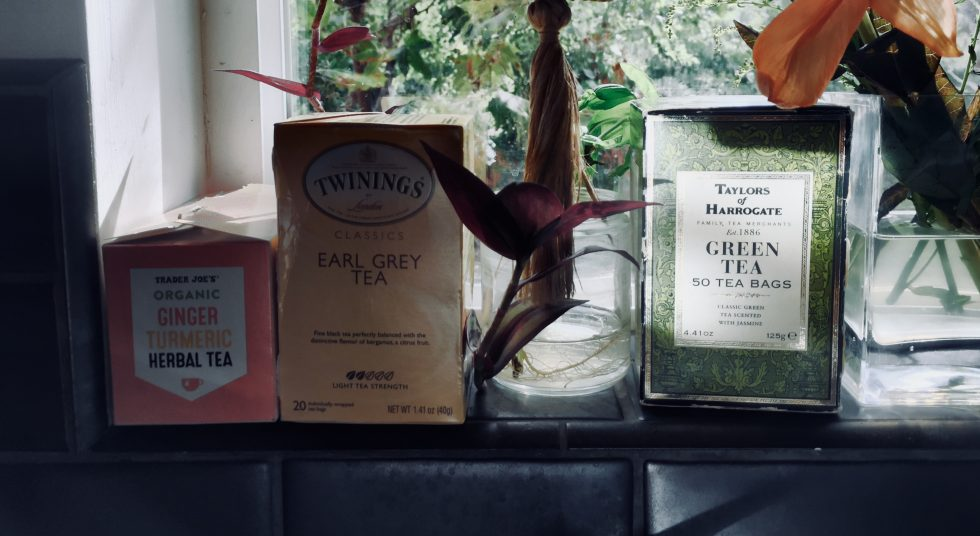 Three boxes of tea on the window sill with flowers